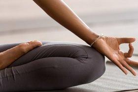 Eine Frau sitzt in meditativer Haltung auf einer Matte