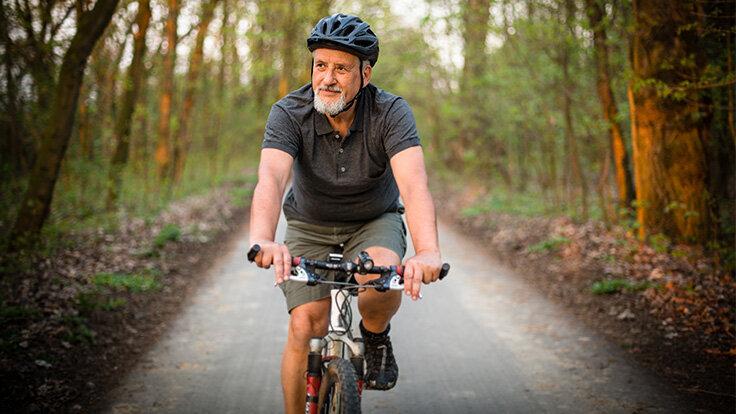 Älterer Mann ist mit dem Rad unterwegs, um durch die regelmäßige Bewegung einer Kniearthrose vorzubeugen.
