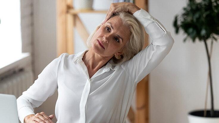 Eine Frau am Schreibtisch dehnt ihren Nacken, da sie Schulterschmerzen hat.