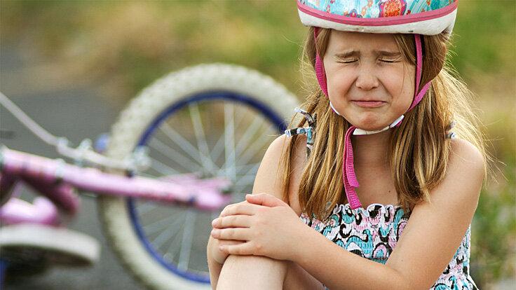 Ein Mädchen sitzt auf dem Boden und weint nach einem Fahrradunfall.