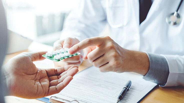 Ein Mann bekommt Medikamente gegen seine Hodenentzündung.
