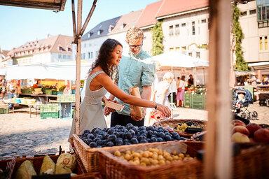 Eine Frau kauft auf dem Wochenmarkt ein.