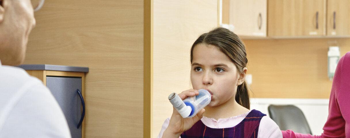 Eine Asthma-Patientin testet beim Arzt einen Inhalator