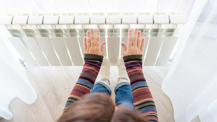 Ein Mädchen wärmt sich die Hände am Heizkörper.