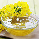 Rapsöl in Glasschüssel und Rapsblüte