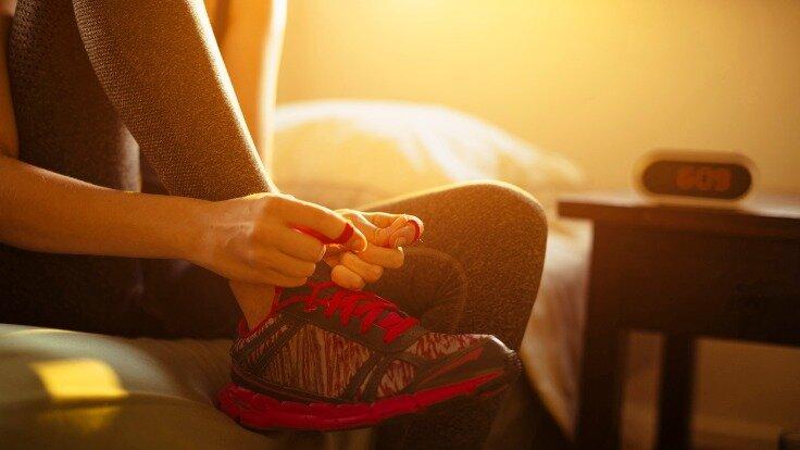Eine Frau schnürt früh morgens ihre Schuhe zum Laufen