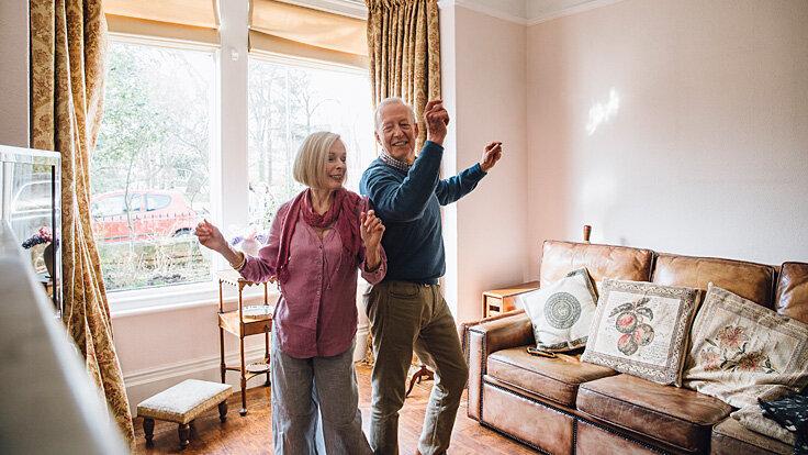 Zwei Senioren tanzen miteinander zu Hause.