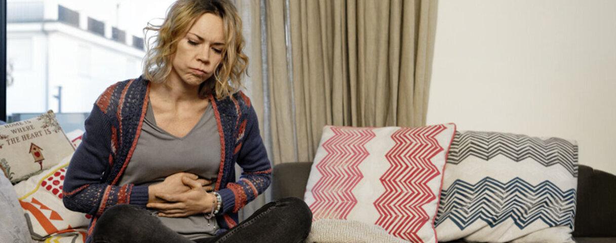 Eine Frau hält sich ihren Bauch, weil sie Gallenschmerzen hat.
