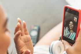 Zwei Freundinnen telefonieren miteinander per Videocall, um einen Lagerkoller während der Coronapandemie zu vermeiden.