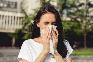 Eine Frau niest, sie hatte eine Sommergrippe.