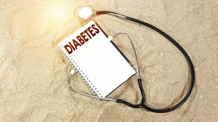 Diabetes-Tagebuch und Stethoskop liegen im Sand