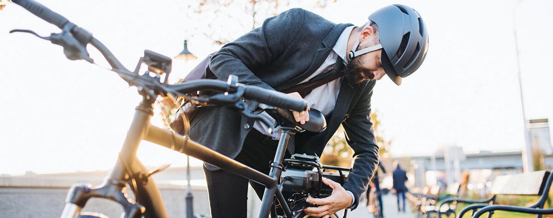 Mann mit Helm prüft vor dem Fahrradfahren, ob sein Rad verkehrstauglich ist.