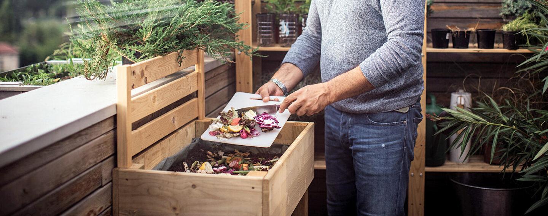 Ein Mann gibt Essensreste in den Kompost auf dem Balkon.