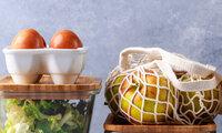 Glasflaschen mit Flüssigkeiten und Container aus Glas mit Lebensmitteln und zubereiteten Speisen