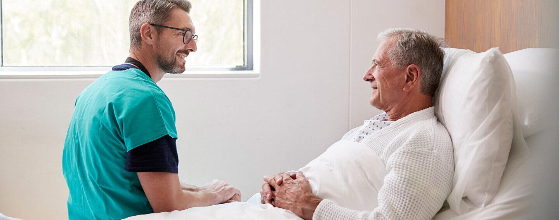 Ein Chirurg spricht mit einem Mann im Krankenbett über mögliche postoperative Schmerzen.