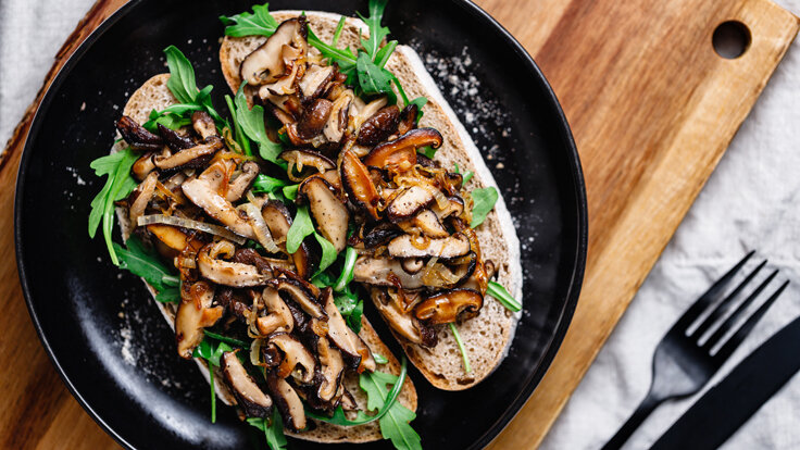 Vegetarisches Pilzgericht mit leckerem Sauerteigbrot und Rucola auf einem schwarzen Teller