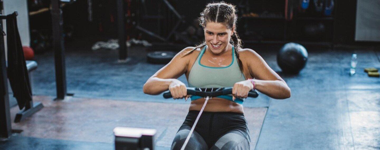 Eine junge Frau trainiert mit dem Rudergerät.