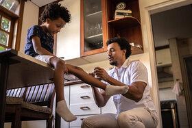 Ein Vater versorgt das verletzte Knie seines Sohnes.