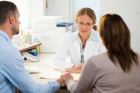 Ein Paar mittleren Alters in einer Beratungssituation mit dem Hausarzt, es besteht Verdacht einer Krebserkrankung