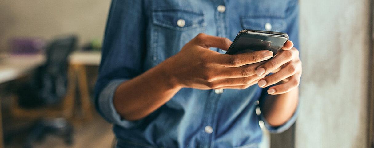 Person tippt auf ihrem Smartphone.