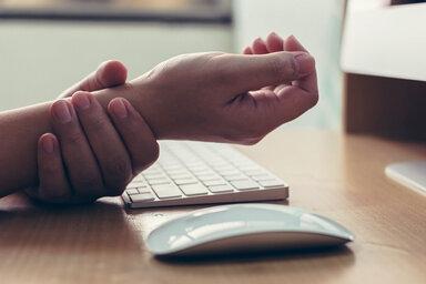 Jemand hält sich das Handgelenk wegen einem schmerzenden Mausarm-Syndrom.