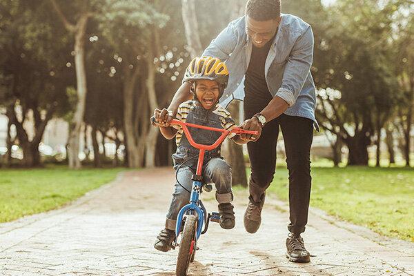 Vater bringt seinem Sohn das Fahrradfahren bei.