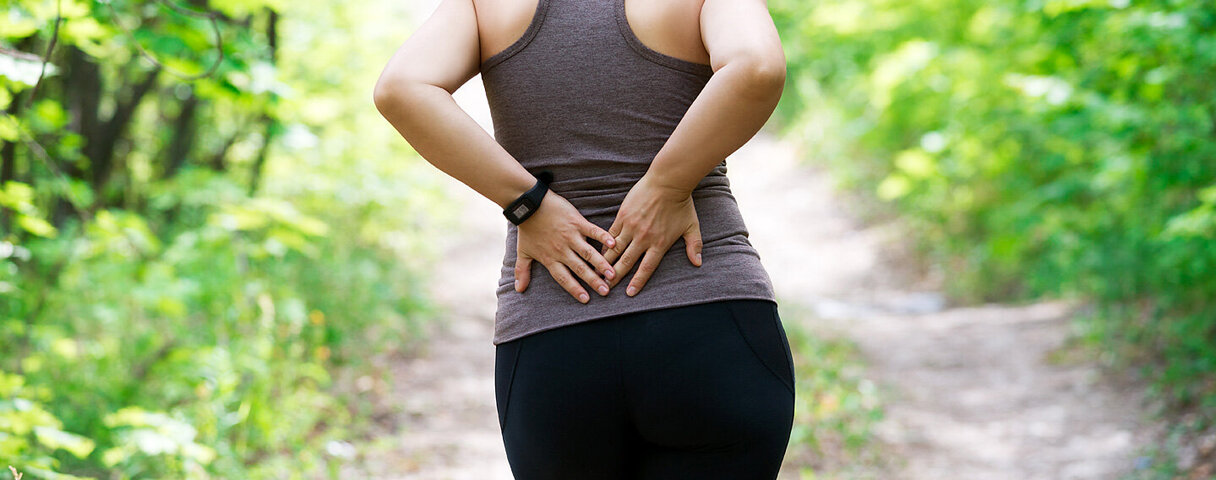 Eine Frau hält sich mit den Händen ihren unteren Rücken.