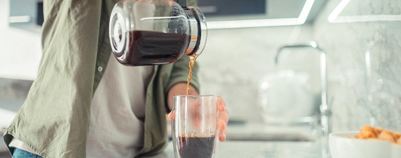 Mann schenkt sich Kaffee ein, doch wie viele Tassen am Tag sind vertretbar?