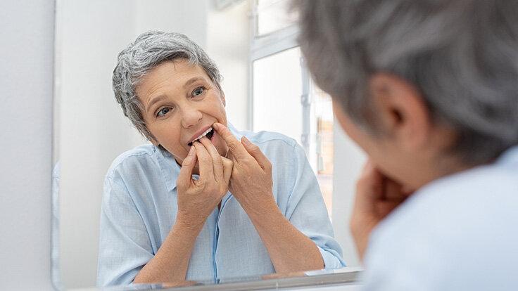Eine Frau reinigt sich ihre Zähne vor dem Spiegel mit Zahnseide.