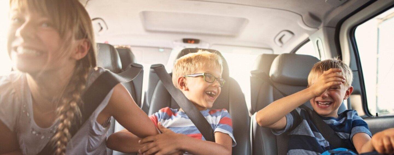Fröhliche Kinder auf der Rückbank eines Autos.