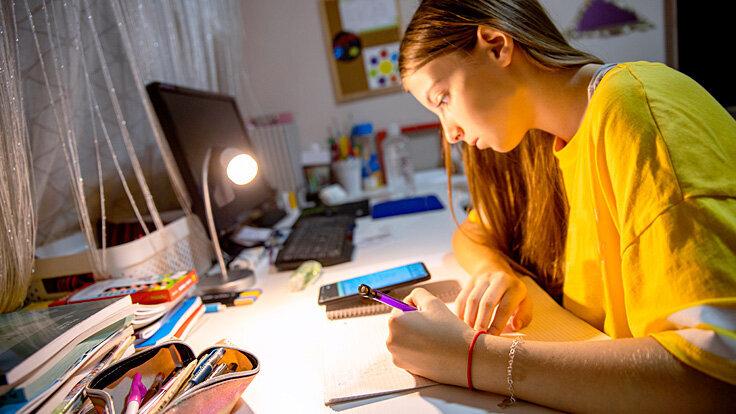 Ein Mädchen macht Hausaufgaben am Schreibtisch und lässt sich durch ihr Smartphone ablenken.