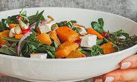 Person hält einen Teller mit einem Feta-Salat in beiden Händen