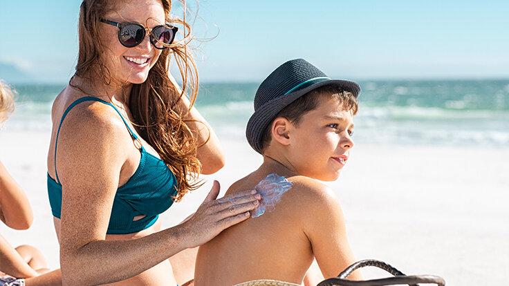 Mutter cremt während dem Sonnenbaden den Rücken vom Kind ein.