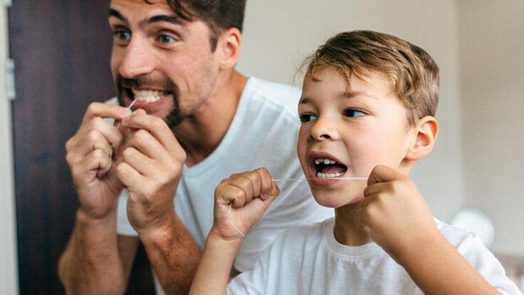 Eine Junge und ein Vater reinigen ihre Zahnzwischenräume mit Zahnseide.