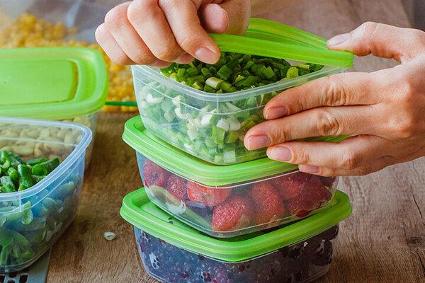 Eine Frau packt Lebensmittel zum Einfrieren in Plastikdosen
