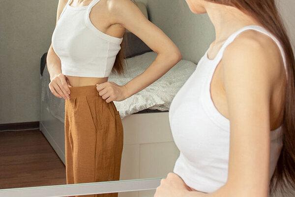 Jugendliche mit Magersucht schaut sich im Spiegel an.