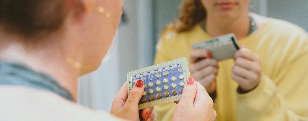 Ein Mädchen schaut sich einen Pillen-Blister an