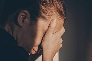 Depressive Frau hält sich die Hände vor das Gesicht
