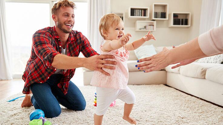 Vater und Mutter bringen ihrem Baby spielend das Laufen bei, es ist eine wichtige Phase in der Entwicklung eines Babys.
