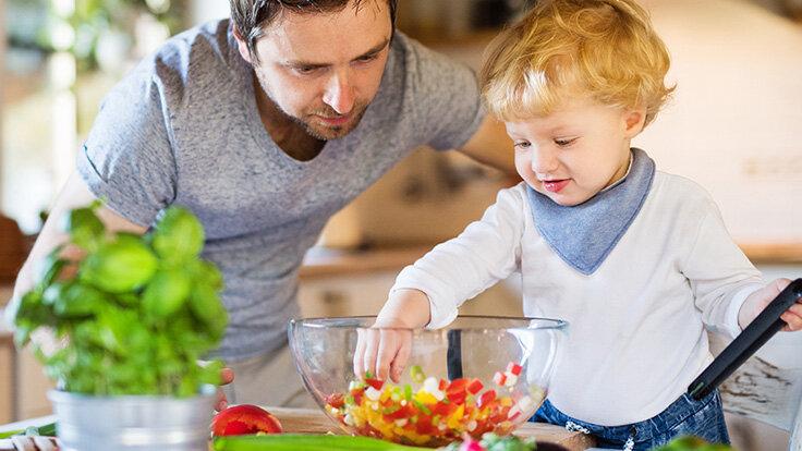 Vater bereitet Gemüse in der Küche zu und lässt sich von seinem kleinen Kind helfen.