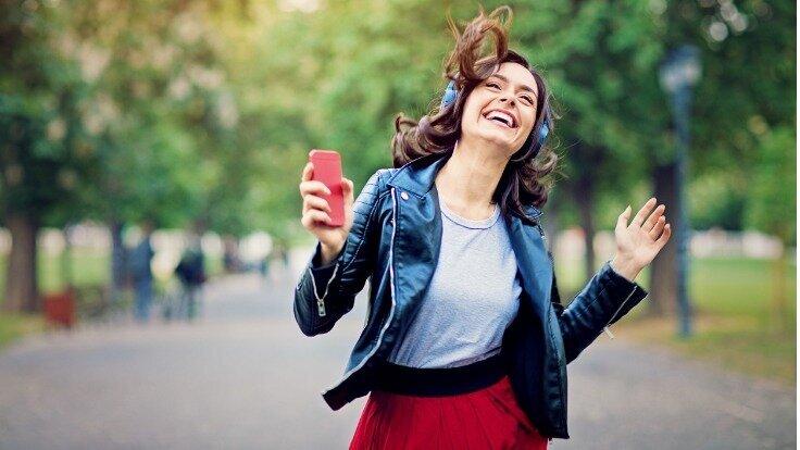 Eine Frau trägt Köpfhörer und hält ein Smartphone in ihrer Hand.