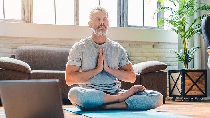Mann macht Entspannungsübung, um psychosomatischen Beschwerden zu lindern.
