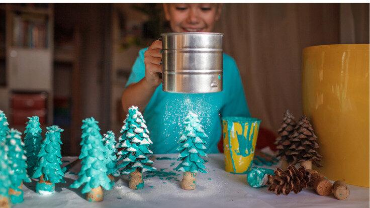Kleines Mädchen verziert ihren selbst gebastelten Tannenzapfen-Wald mit Kunstschnee.