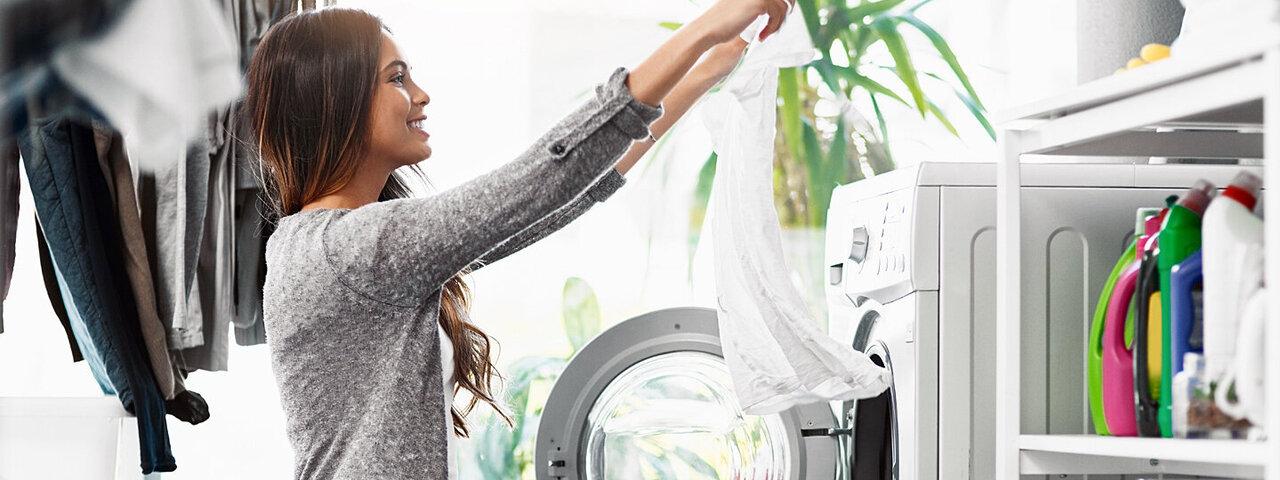 Eine junge Frau nimmt frisch gewaschene und fleckenfreie Wäsche aus der Waschmaschine.