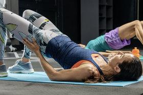 Frau macht eine Rückenübung im Fitnessstudio.