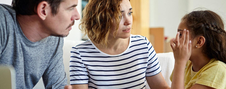 Eltern hören ihrem Kind zu, das von Kopfschmerzen und Migräne berichtet.
