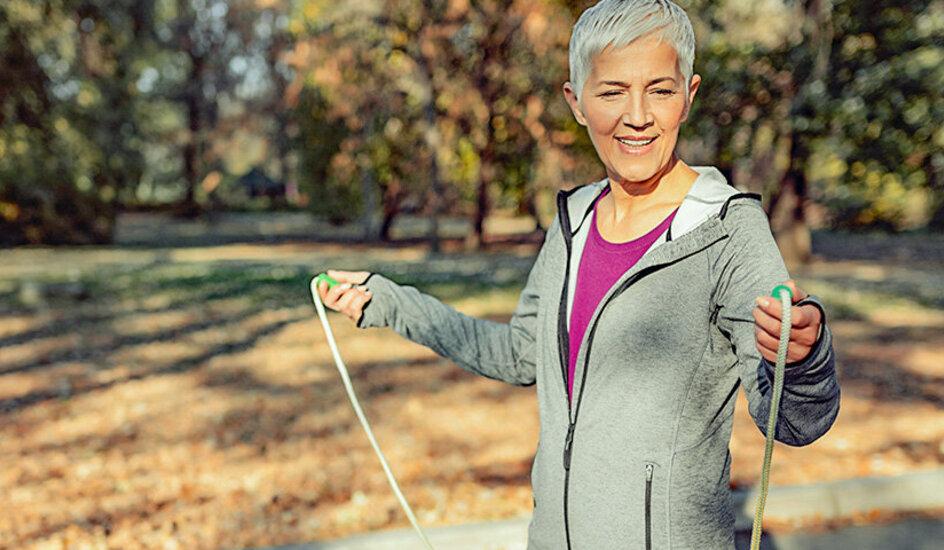 Eine Frau geht im Wald Seilspringen