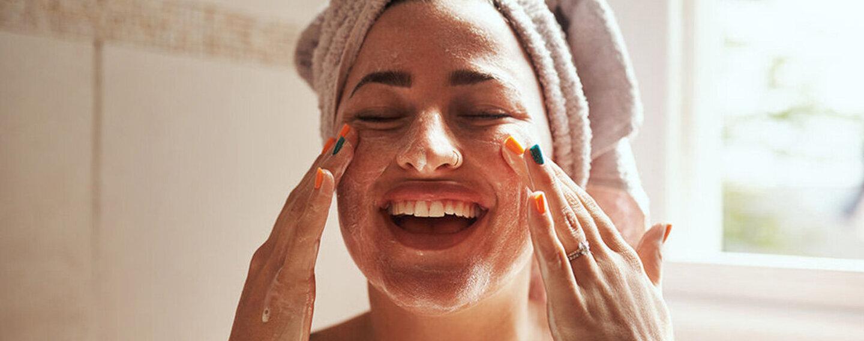 Wellness zu Hause: Frau reinigt ihr Gesicht.