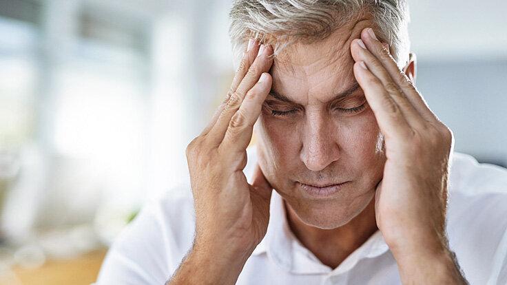 Ein Mann massiert seine Schläfen; er hat Kopfschmerzen.