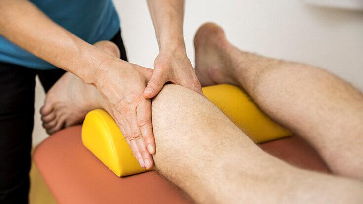 Eine Person erhält eine physiotherapeutische Behandlung an den Waden.